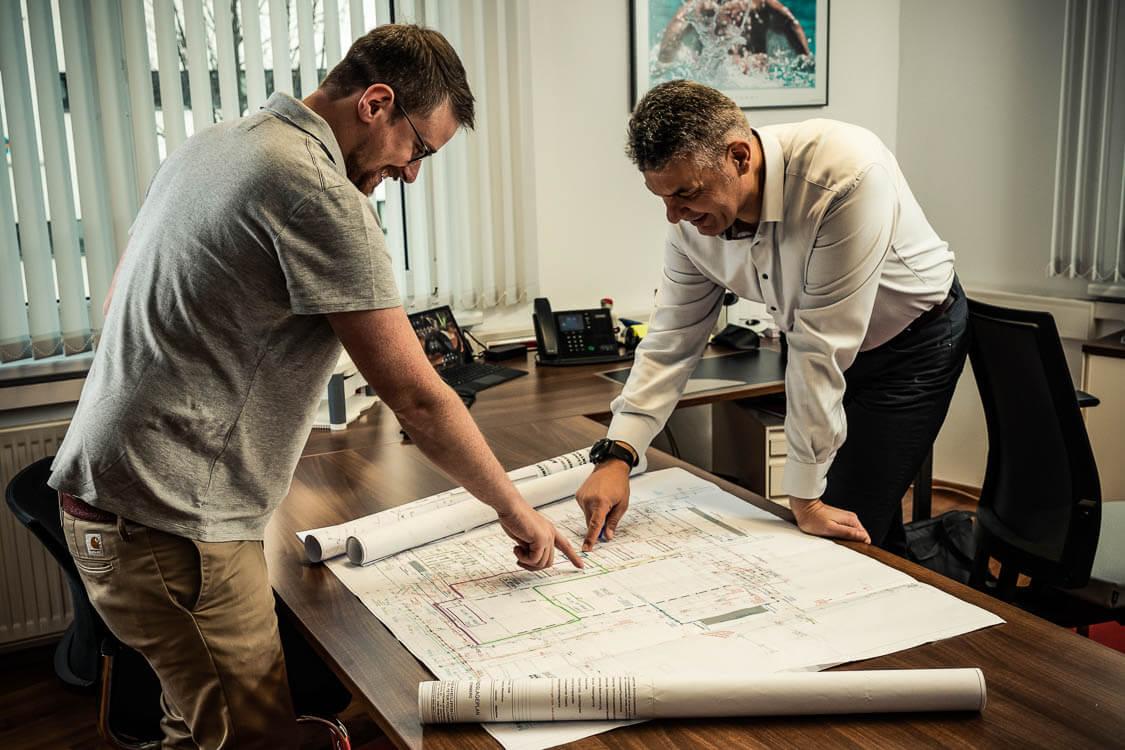 Zwei DAWI Mitarbeiter in einem Büro untersuchen einen Kanalnetzplan