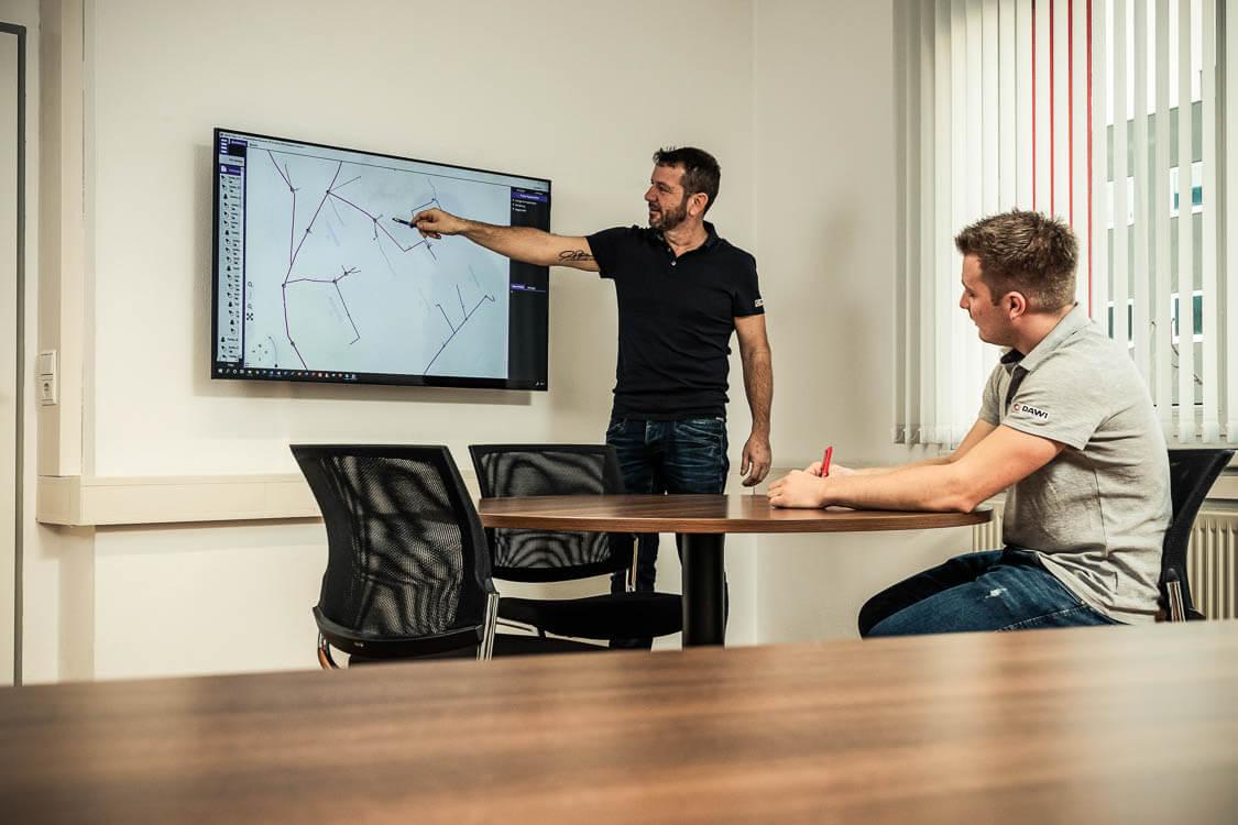 DAWI Mitarbeiter zeigt Kunden auf einem Bildschirm das digitale Kanalnetz