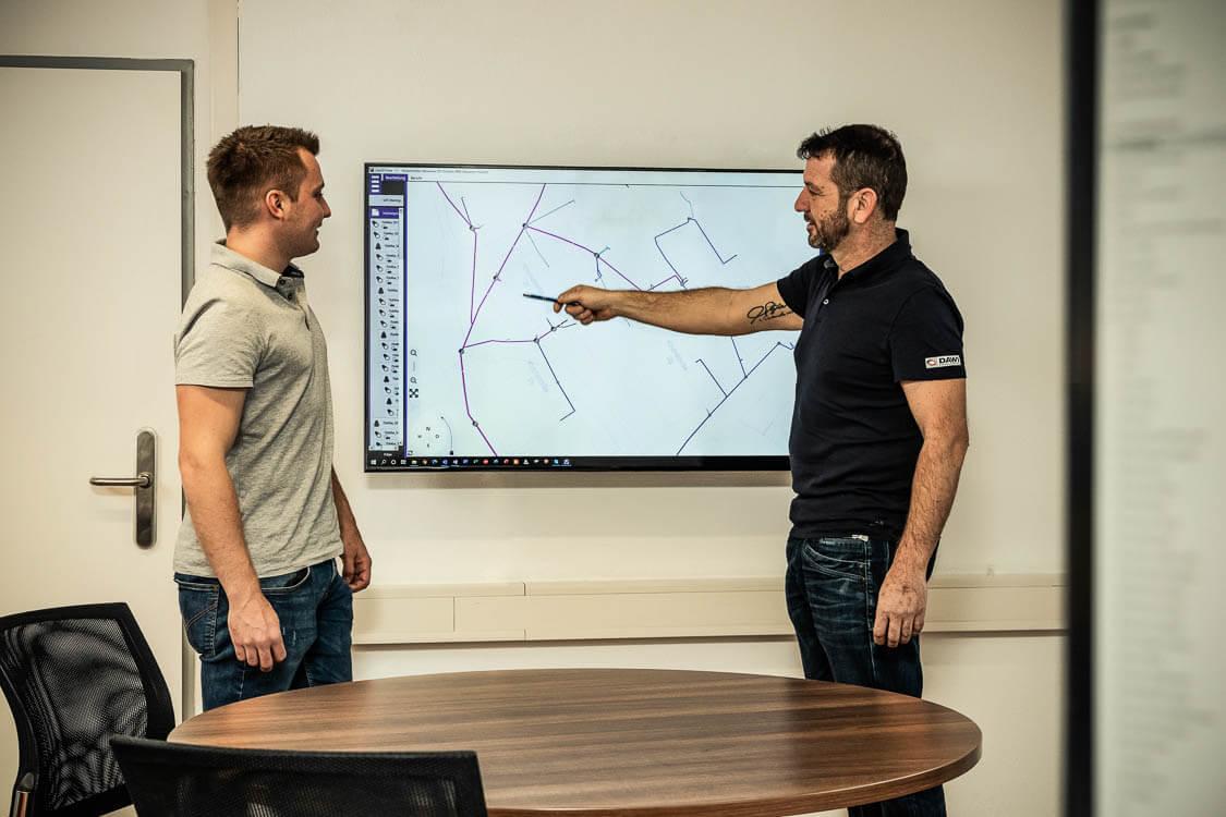 DAWI Mitarbeiter zeigt mit einem Stift auf einen Screen und erklärt digitales Kanalnetz