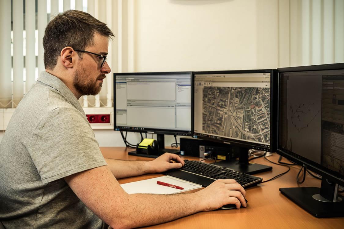 DAWI Mitarbeiter sitzt am Schreibtisch vor drei Bildschirmen und erstellt einen dreidimensionalen Lageplan