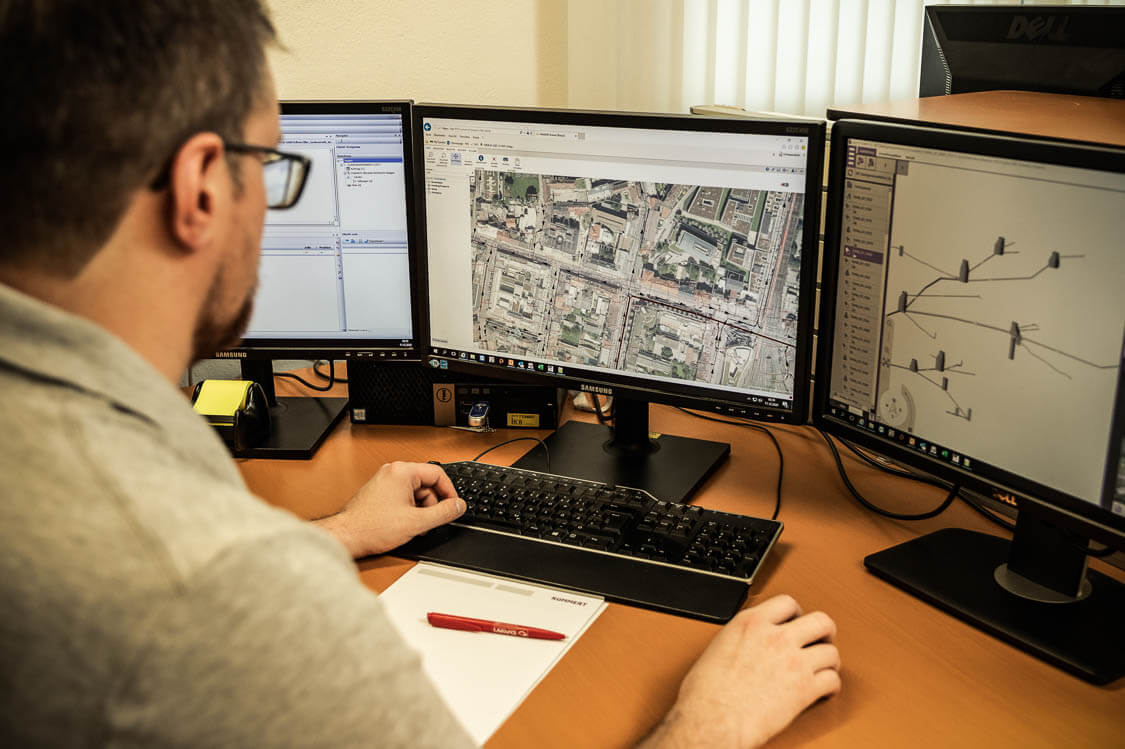 Mitarbeiter am Schreibtisch vor drei Bildschirmen erstellt einen digitalen Kanalnetzplan