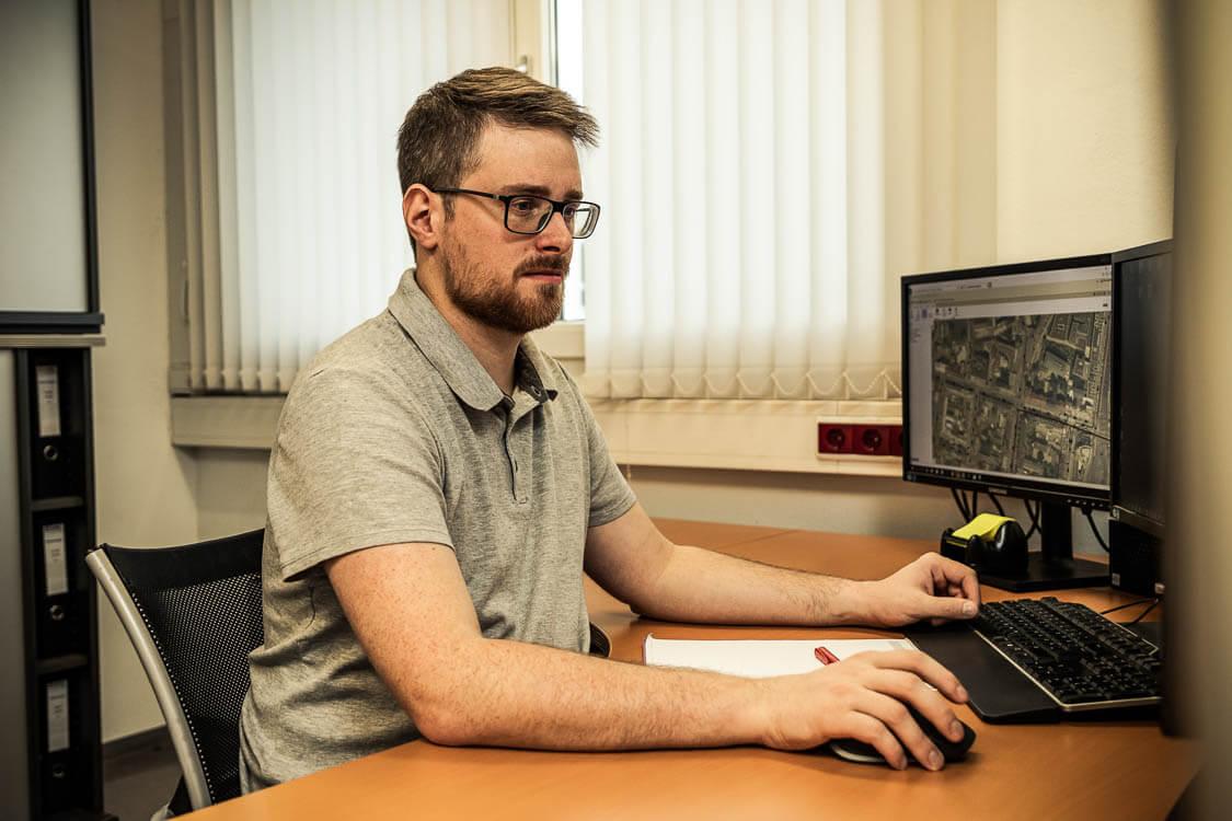 Mitarbeiter arbeitet am PC an einem Kanalnetzplan für Gemeinden