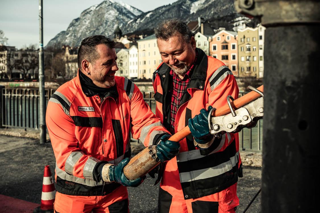 Zwei DAWI Mitarbeiter bei der Arbeit halten lächelnd einen Schlauch