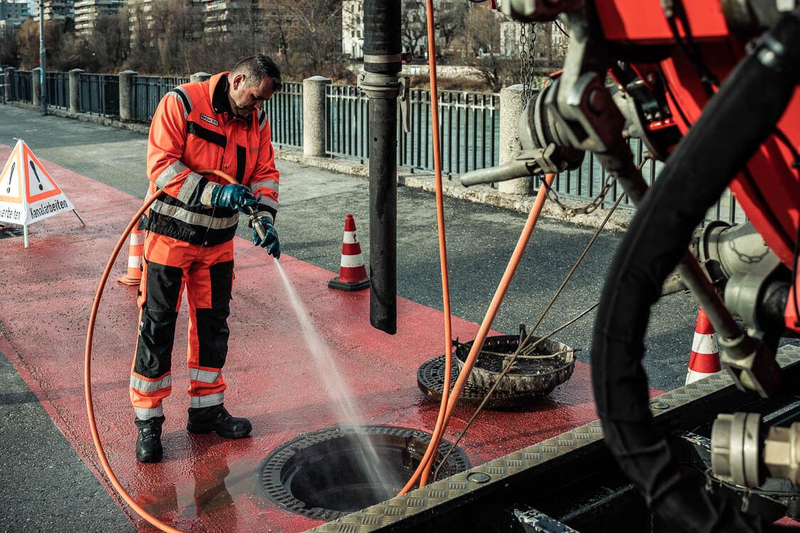 DAWI Mitarbeiter hält Hochdruckschlauch und löst Ablagerungen von Kanalwänden