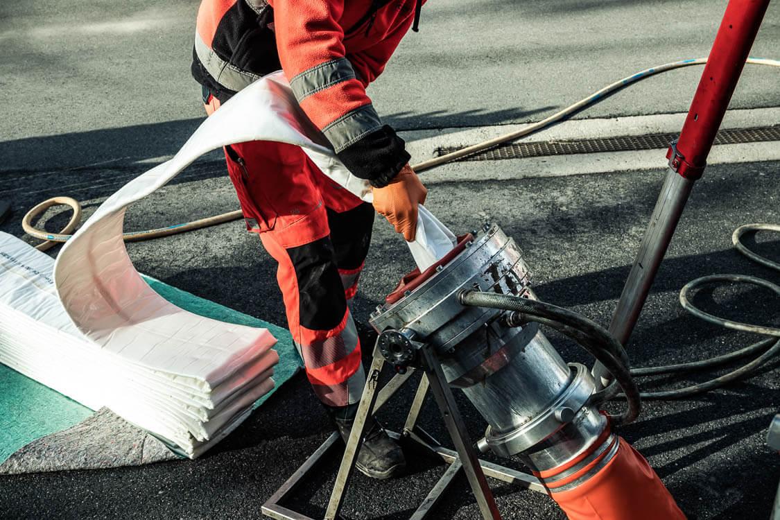Closeup eines DAWI Mitarbeiters, der einen Textilschlauch in das defekte Rohr schiebt