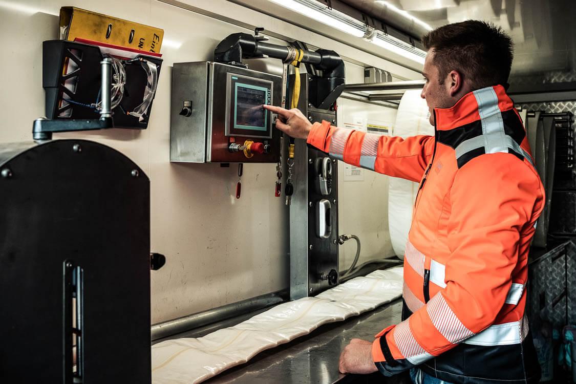 DAWI Mitarbeiter beim Bedienen der Maschine für die Tränkung des Schlauchs in Harz