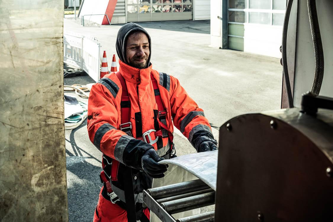 Mitarbeiter steht vor Maschine, die den Schlauch in Harz tränkt