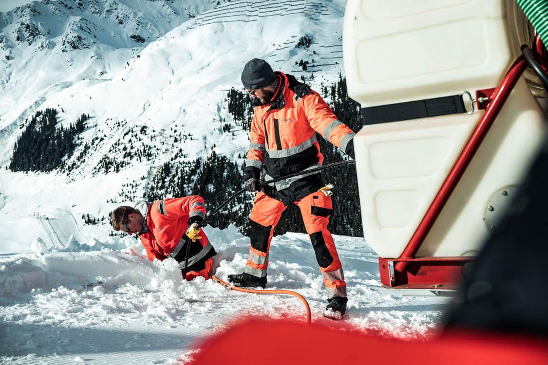 Zwei DAWI Mitarbeiter reinigen Kanal der Bergbahnen in exponierter Lage