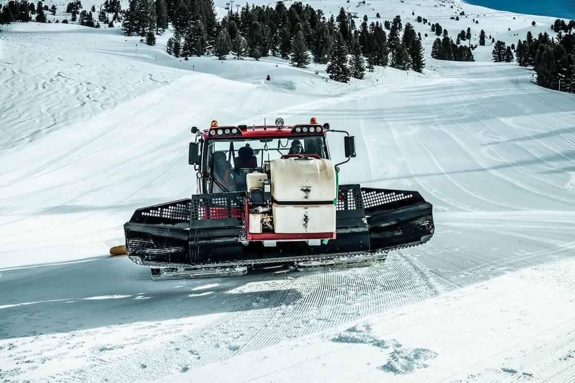 DAWI Mitarbeiter transportiert Gerätschaften für Kanalreinigung am Berg mit einer Pistenraupe